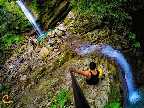 یک مرد در حال سلفیگرفتن با آبشار دارنو