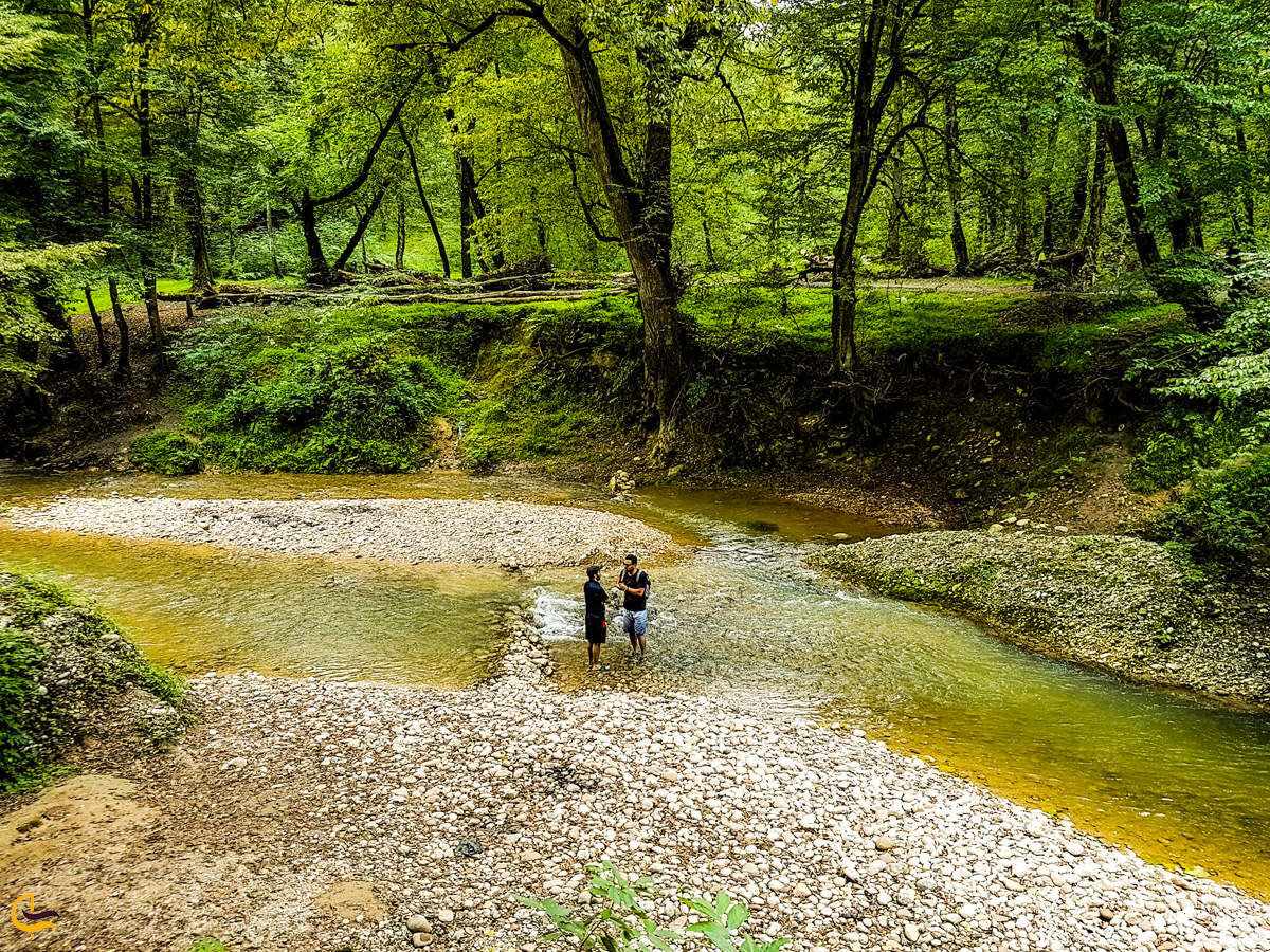 دو مرد در حال پیادهروی در رودخانه نزدیک آبشار پلنگ دره