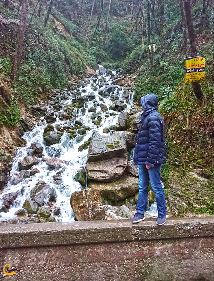 مردی ایستاده کنار آبشار