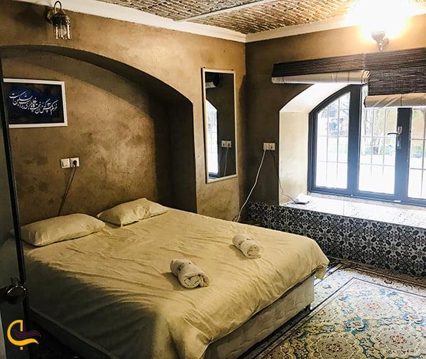 تصویر اتاق بسیا زیبا و لوکس با پنجره ای روبه منظره چشم نواز باغ ایرانی در شیراز